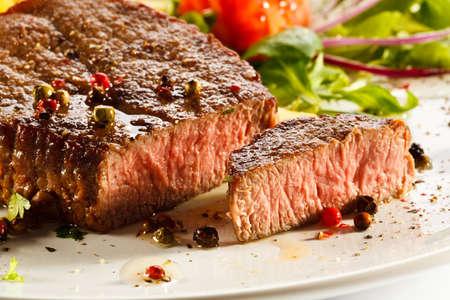 carne asada: Carne a la parrilla, papas fritas y legumbres Foto de archivo