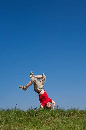 A boy doing a handstand outdoors Imagens