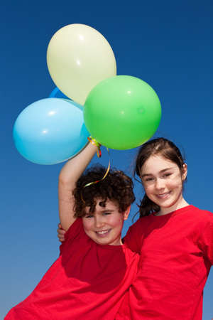 13 15 years: Girl and boy playing with balloons outdoors