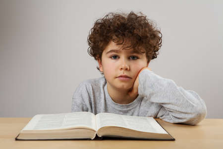 revising: Boy reading a book on the table Stock Photo