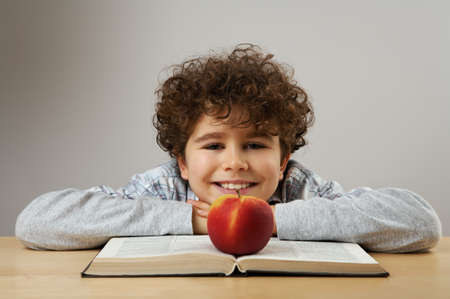 revising: Boy reading a book with an apple on the table
