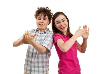 aplaudiendo: Chica y chico posando sobre fondo blanco
