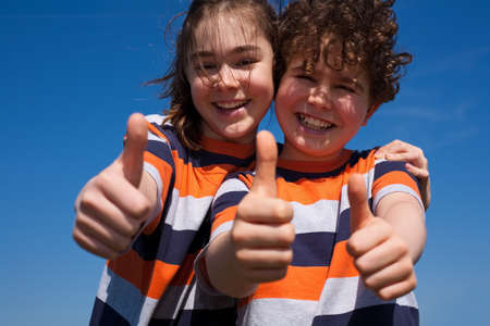 10s: Siblings showing thumbs up