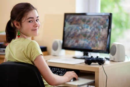 10's: Girl playing a computer game Stock Photo