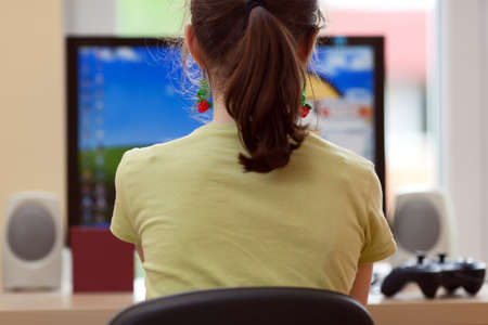 Girl sitting in front of a computer photo