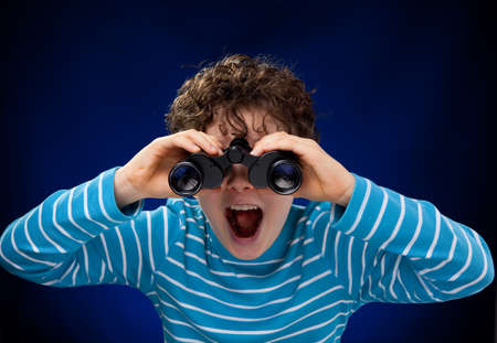 inspector kid: Boy looking through binoculars Stock Photo