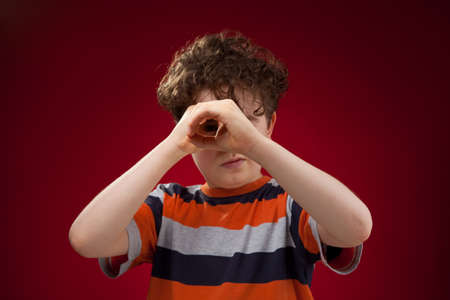 inspector kid: Boy looking on red background  Stock Photo