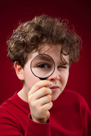 Boy using a magnifying glass  photo