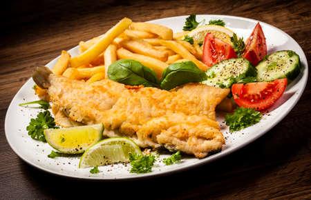 fish and chips: Filete de pescado frito, patatas fritas con verduras Foto de archivo