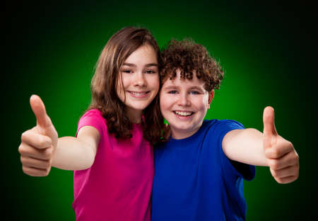Girl and boy showing thumbs up on green background photo