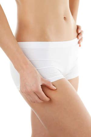 muslos: Delgado pellizcos muslo mujer sobre fondo blanco