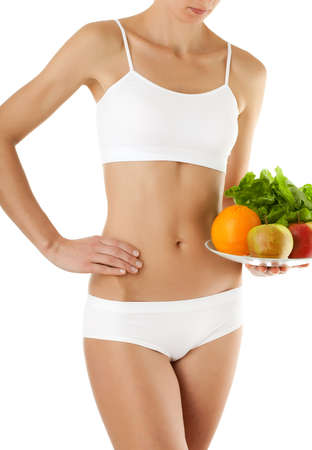 Slim woman holding a plate of fruits and vegetables on white background Stock Photo