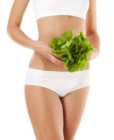 white singlet: Slim woman holding vegetables on white background