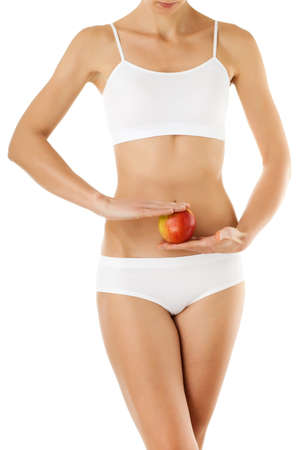 Slim woman holding an apple on white background