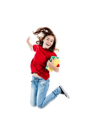 Girl jumping with books on white background photo