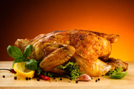 Roasted whole chicken on chopping board