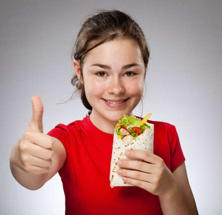 tied hair: Girl holding pita bread while showing thumbs up Stock Photo
