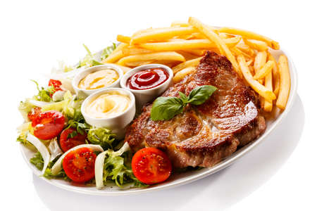 Grilled steak with fries and salad on white background photo