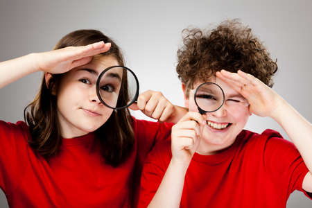 inspector kid: Girl and boy looking into magnifying glass on gradient gray background