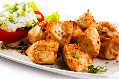 nuggets: Grilled meat chunks with tomato on white background