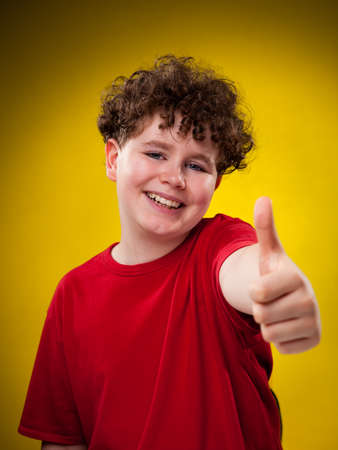 Boy showing thumbs up on isolated yellow gradient background photo