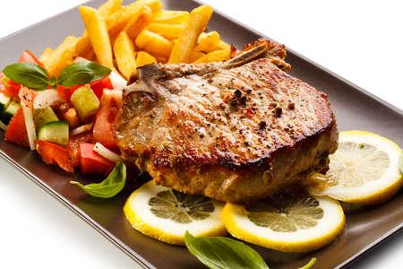 Gebakken karbonade met frites en salade Stockfoto