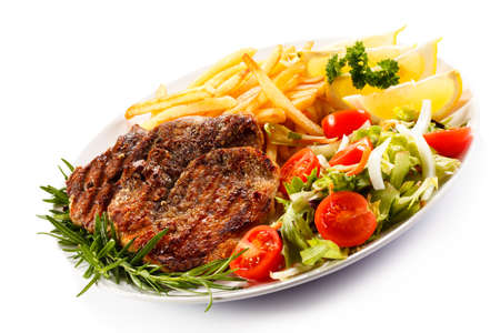 Grilled steak with chips and salad on white background