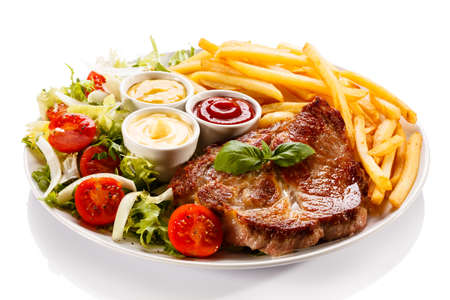 steak dinner: Grilled steak with fries and salad on white background Stock Photo