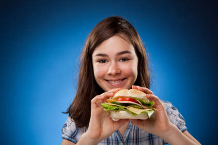 Girl holding burger on gradient blue background  photo