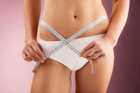 woman measuring waist: Woman measuring her waist Stock Photo