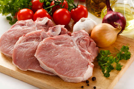 beef meat: Raw meat on cutting board with vegetables Stock Photo