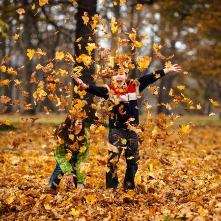 hojas antiguas: Ni�o y ni�a jugando con las hojas ca�das en oto�o Foto de archivo