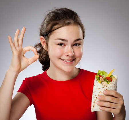 mexican girl: Girl eating chicken wrap