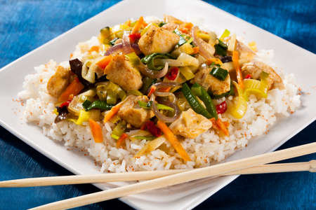 Stir-fried chicken and vegetables served with rice photo