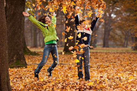 persona saltando: Ni�o y ni�a jugando con las hojas ca�das en oto�o Foto de archivo