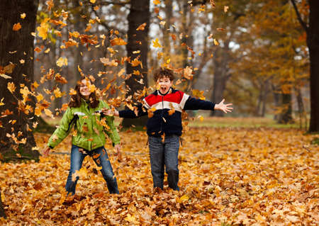 Boy and girl playing with fallen leaves in autumn 免版税图像