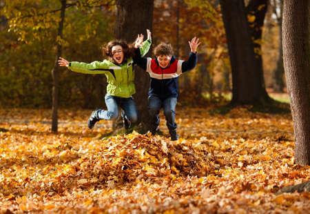 Niño y niña jugando con las hojas caídas en otoño Foto de archivo