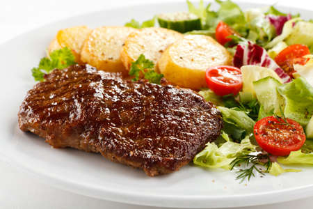 baked potatoes: Grilled steak served with baked potatoes and vegetables
