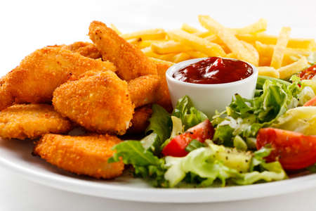 Fried chicken nuggets with French fries and vegetables