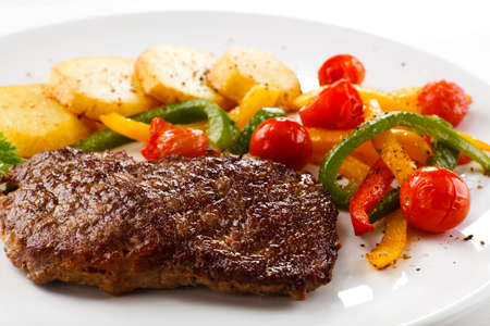 Grilled steak with baked potatoes and vegetables photo