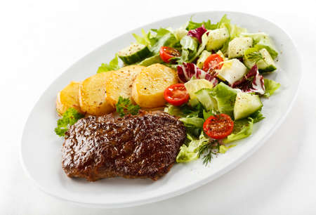 Grilled steak served with baked potatoes and vegetables photo