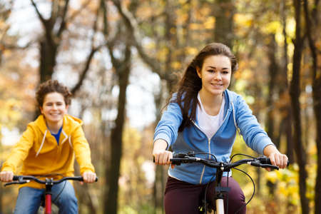 bicyclists: Girl and boy riding bikes in the forest Stock Photo