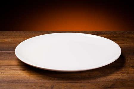 Una placa blanca vacía en mesa de madera
