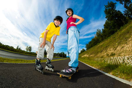 rollerblade: Girl skateboarding and boy rollerblading