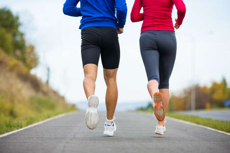 back view man: Lower half of man and woman jogging on the road