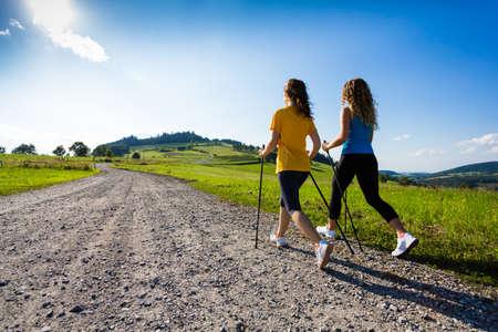 Zwei Mädchen, die Nordic-Walking-