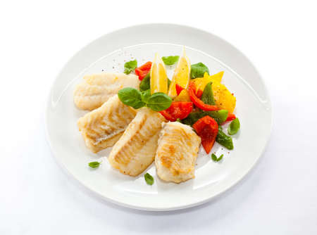 Top view of baked fish fillet with fries and vegetables