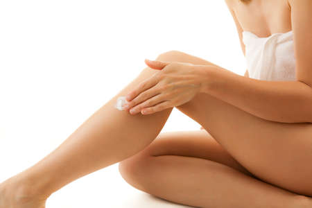 moisturize: Woman applying cream on her legs Stock Photo