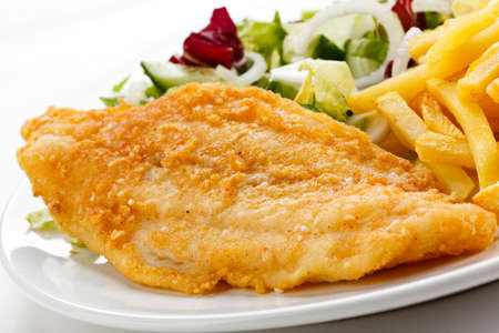 Close up of fried fish fillet with fries and vegetables
