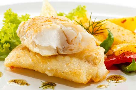 plato de pescado: Close up de filete de pescado frito con papas fritas y verduras